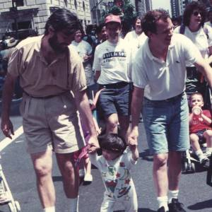 Michael Cudney, his husband Keith Kelly, and their son Chris Kelly in one of their first parades.